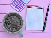 Notebook with calculator and coffee cup on purple table Stock Image