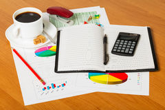 Notebook, calculator, cup coffee and office supplies on desktop background. Stock Images