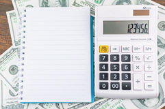 Notebook and calculator on dollar bill background Royalty Free Stock Image