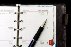 Notebook, calendar and pen. Pocket planner with pen, close up royalty free stock photography
