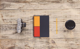 Notebook, camera, coffee cup, pencil on old wooden boards. View from above. Hipster style. Top view with copy space. Free space fo Stock Photography