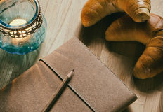 Notebook, candle lantern and croissants Stock Photography