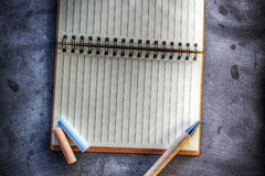 Notebook and chalks on a blackboard Royalty Free Stock Image