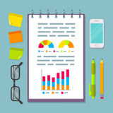 Notebook with charts on business planning table. Open vertical spiral notebook with business plan charts, graphs and diagrams. Business planning table with top Royalty Free Stock Photos