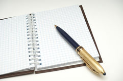 NOTEBOOK IN CHECK III. PHOTO WITH NOTEBOOK AND GOLDEN PEN Stock Image