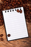 Notebook with coffee beans Royalty Free Stock Photography