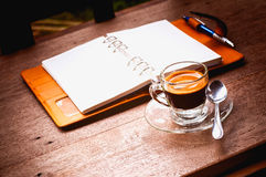 Notebook and coffee cup on old wooden background, business conce Royalty Free Stock Image