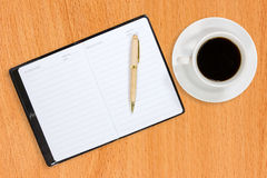 Notebook and coffee cup on the table Royalty Free Stock Photography