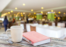 Notebook and coffee cup on wooden with blurred of restaurant bac Stock Images