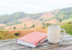 Notebook and coffee cup on wooden table with blurr background Royalty Free Stock Image