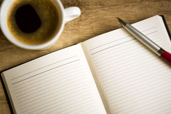 Notebook with coffee cup on wooden table Stock Photography