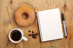 Notebook and coffee with donut Stock Photos