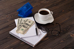 Notebook, coffee, money, piggy bank in the form of house Royalty Free Stock Image