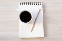 Notebook, coffee and pen on wooden table stock photo