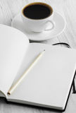 Notebook and coffee on a white background. Notebook and coffee on the white wooden background Stock Photos