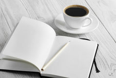 Notebook and coffee on a white background. Notebook and coffee on the white wooden background Royalty Free Stock Photos
