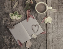 Notebook and coffee on wooden table decorated with dried leaves Royalty Free Stock Photos