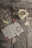 Notebook and coffee on wooden table decorated with dried leaves Royalty Free Stock Photo