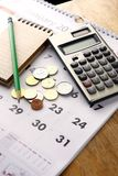 Notebook, coins, calendar, calculator and pencil on a table Royalty Free Stock Photo