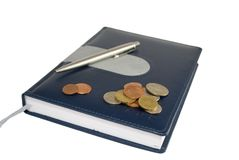Notebook with coins and pen Royalty Free Stock Photography