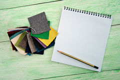 Notebook and colored fabric Royalty Free Stock Image