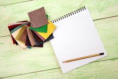 Notebook and colored fabric Royalty Free Stock Images
