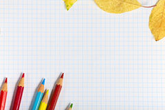 Notebook with colored pencils and autumn leaves Stock Photos