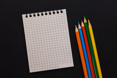 Notebook and colored pencils on a black background Royalty Free Stock Photography