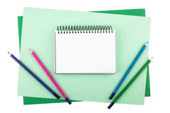 Notebook and colored pencils on sheets of textured paper Stock Image
