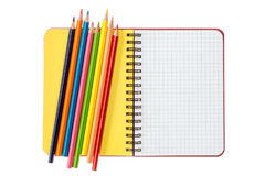 Notebook and colored pencils on white Stock Photography