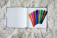 Notebook and colored pens Stock Photography