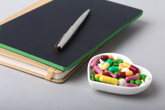 Notebook and colorful assortment pills, capsules on plate. Royalty Free Stock Image