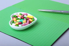 Notebook and colorful assortment pills, capsules on plate. Royalty Free Stock Images