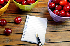 Notebook and colorful bowl with cherries Stock Image