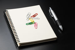 notebook with colour clip and pen on black table. Royalty Free Stock Photo
