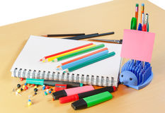 Notebook, coloured pencils and office supplies Stock Photos