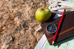 Notebook, compass, apple, rope on stone background Royalty Free Stock Photos