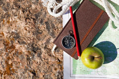Notebook, compass, apple, rope on stone background Royalty Free Stock Photo