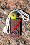 Notebook, compass, apple, rope on stone background Stock Images