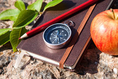 Notebook, compass, apple, rope on stone background Royalty Free Stock Photography