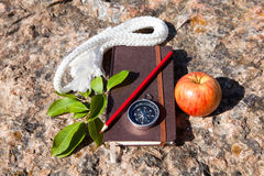 Notebook, compass, apple, rope on stone background Royalty Free Stock Image