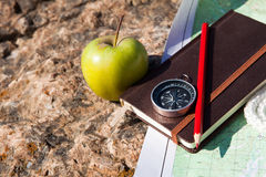 Notebook, compass, apple, rope on stone background Stock Image