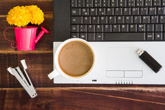 Notebook computer with coffee cup, computer and flower. View fro stock photos