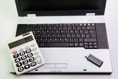 Notebook computer on the desk.Calculators,USB flash drive stick Royalty Free Stock Photo