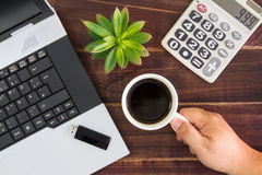 Notebook computer on the desk.Calculators,USB flash drive stick,coffee cup.  stock photo