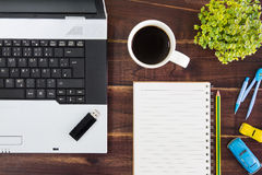 Notebook computer on the desk.USB flash drive stick,paper,coffee cup royalty free stock photos