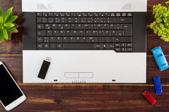 Notebook computer on the desk,USB flash drive stick,smartphone.  royalty free stock image