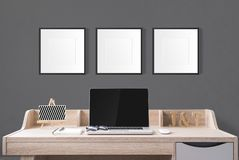 notebook computer and stationery on working table with blank photo frames in the studio with dark grey wall. stock images