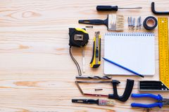 Notebook and construction tools, on a wooden table. The workplace of the foreman. The theme of home and professional repair, stock images