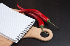 Notebook for cooking recipes and red chili peppers Royalty Free Stock Images